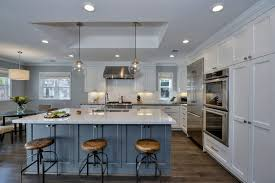 Luxury kitchen with white shaker cabinets, blue island with white marble  counters and globe pendant