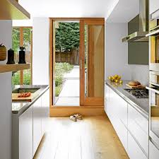 here wide handleless units and wood flooring work in unison to lead the eye down towards a glass door which in turn leads out to the garden path