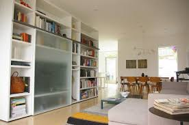 white bookcase with glass doors ideas for modern living room with frosted glass partition view to backyard and beige sectional