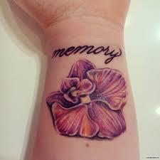 орхидея с надписью Memory тату на запястье у девушки добавлено