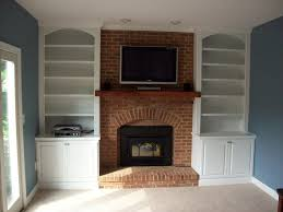 brown brick fireplace with brown wooden mantel shelf added by double white wooden bookshelves and blue