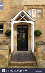 black front door and white painted porch on a cotswold limestone house
