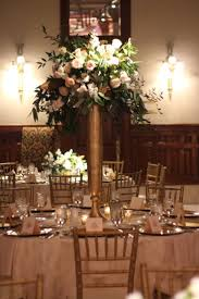 Another option for the tall centerpiece. using our tall gold metal vase on  the navy blue linens with a beautiful fresh flower design to match
