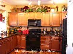 Decorating top of cabinets. Layering iron scroll with a basket and bring  sympetrical