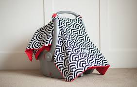 black and white rainbow shaped designs adorn the solomon canopy this fun yet classy print dresses up any baby carrier red minky dots the interior