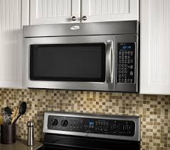 wood wall mounted microwave shelf above stove under cabinet painted with white color and light brown mosaic kitchen backsplash ideas