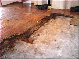 installing laminate wood flooring floor in basement around door frame stone fireplace over concrete slab glue