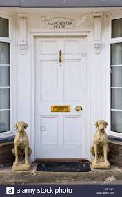 white painted wooden paneled front door of house with brass letterbox knocker and stone hound dogs sitting outside
