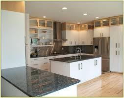 white kitchen cabinets with dark green granite countertops
