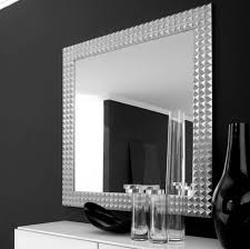 interior square mirror with silver frame placed on the black wall feat white wooden table