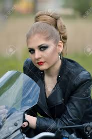 professional unusual hairstyle and makeup stunning fashionable dangerous angry serious biker with smokey makeup eyes make up red lips with