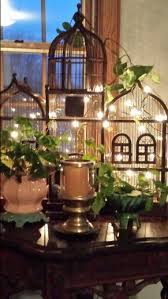 Adding a bird cage into the decor mix of a room is like adding the bohemian vibe, the victorian feel, or steampunk touch. Bird Cage Decorated With Lights And Plants Bird Cage Decor Vintage Bird Cage Bird Cage