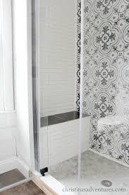 built in shower seat bench glass shower door patterned tile and subway tile