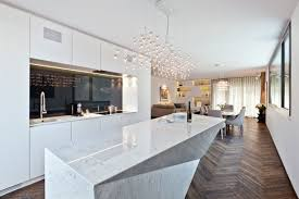 interesting polished white granite kitchen island come with crystal clear modern chandelier and chevron pattern wood