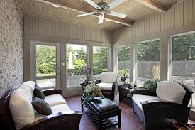 Attractive sunroom with exposed beams, brick wall and fan