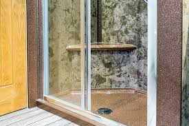 bespoke shower tray in sparkle granite with contrasting wall panels in coffee cream with a sitting ledge