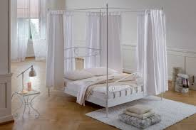 appealing white metal diy canopy bed and small side table inside wide bedroom with hardwood flooring
