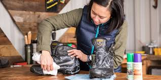 a woman cleaning and conditioning leather hiking boots