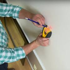 man using an electronic stud finder and marking the location of a wall stud