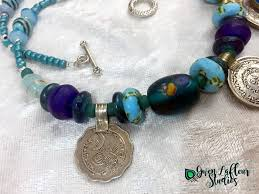 on the sides of the necklace there are more recycled glass african beads plus re fired beads from nepal smaller coin pendants are intersd between