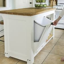a kitchen island with trash storage