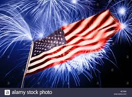 American Flag At Night With Fireworks Exploding In The Air