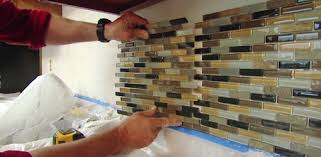 installing a diy mosaic glass tile backsplash in a kitchen