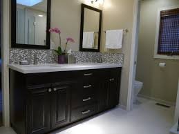 maple with dark stained cabinet with quartz countertop and framed mirrors