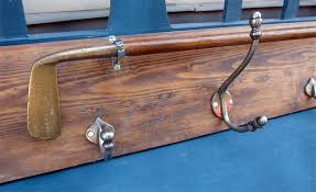 this hook board has been made in house from reclaimed floorboards we have stained the board polished and waxed it and then mounted a old golf club and