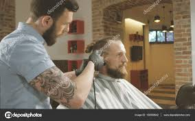 mens hairstyling and haircutting with hair clipper in a barber shop or hair salon stock