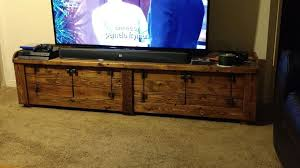 amusing walnut finish wood tv stand featuring double glass door cabinets and 3 small rectangular pull out drawers