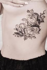 женская татуировка с цветами пиона и змеей на боку Tattoodesign