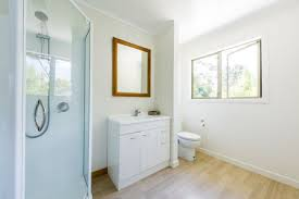 view past shower to sink and toilet in sunny bathroom