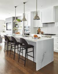 three dark gray velvet stools sit at a white kitchen island fitted with a calcutta quartz waterfall countertop finished with a stainless steel sink with a