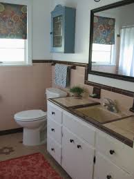 bathroom, peach tile with reddish-brown trim. Blue and coral accessories.