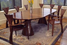 expanding wood oval tinsman dining table with organic base and sculptural finback chairs hand made by