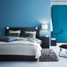 a modern blue and black bedroom with malm bed in black and pax wardrobe in high