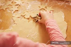 Over Shoulder Cropped View Of Girl Making Star Shape Pastry At