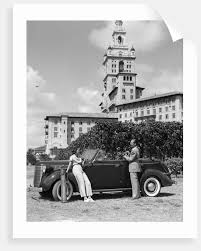 1930s couple with golf clubs standing by a car in front of the biltmore hotel miami