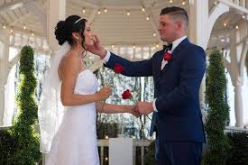 rebecca poncsak left and scott deutscher hold roses after exchanging rings during their wedding