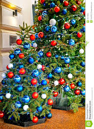 Red, blue and white decorating balls on the christmas tree at th