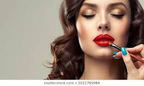 makeup artist applies red lipstick beautiful woman face hand of make up master