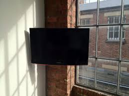 corner wall mount tv storage with red brick wall panels and large glass window ideas