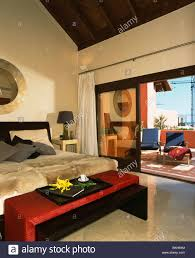Spanish Bedroom Furniture Red Stool Below Bed With Faux Fur Throws In Modern Spanish Bedroom