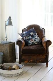 beautiful corner of a living room interior old worn leather armchair with a accent pillow