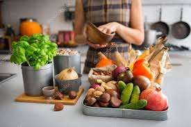 kitchen counter with food. A Tray Full Of Autumn Fruits, Nuts, And Vegetables Sits On Kitchen Counter. Next To The Tray, Wooden Cutting Board Featuring Fresh Basil Plant Counter With Food