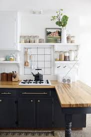 retro inspired black cabinets with light colored butcher block countertops