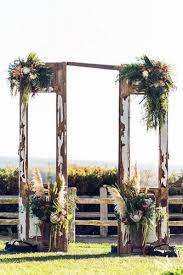 old door wedding decoration ideas the altar is decorated with flowers and greenery vitae weddings via