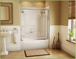 white fiberglass bathtub with glass wall divider and door combined with white wall panel and small
