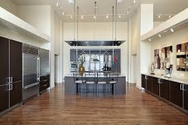 large kitchen with hardwood flooring and marble countertops on both kitchen counters and center island